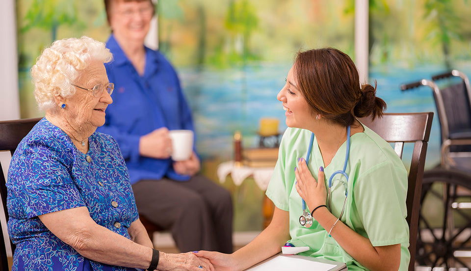 An elderly women in a nursing home sitting and with a young nurse to highlight the venerable people in our communities.