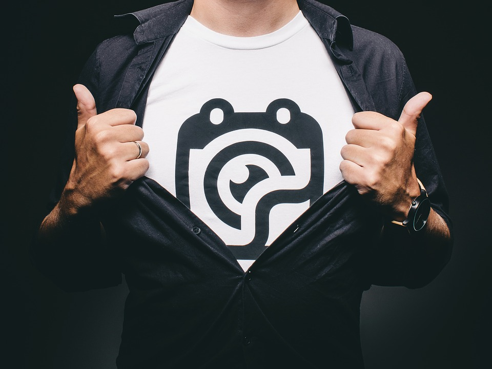 A man pulling open his button up to reveal a white T-shirt with a black printed logo on it.