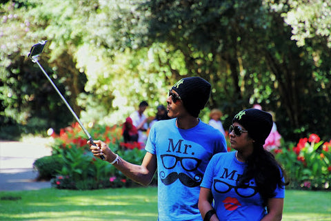 Couple with custom shirts taking pictures at the park
