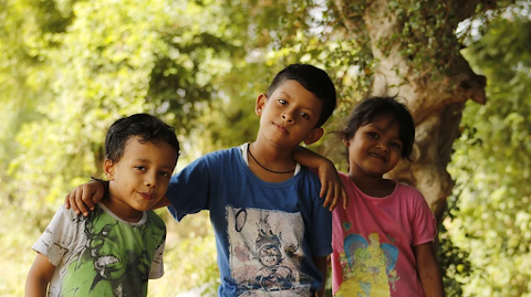 three kids wearing colorful blue, red and green graphic t-shirts