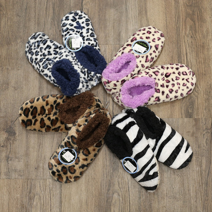 Four pairs of Snoozie Slippers. All different patterns and colors that are available at the Gift Shop.