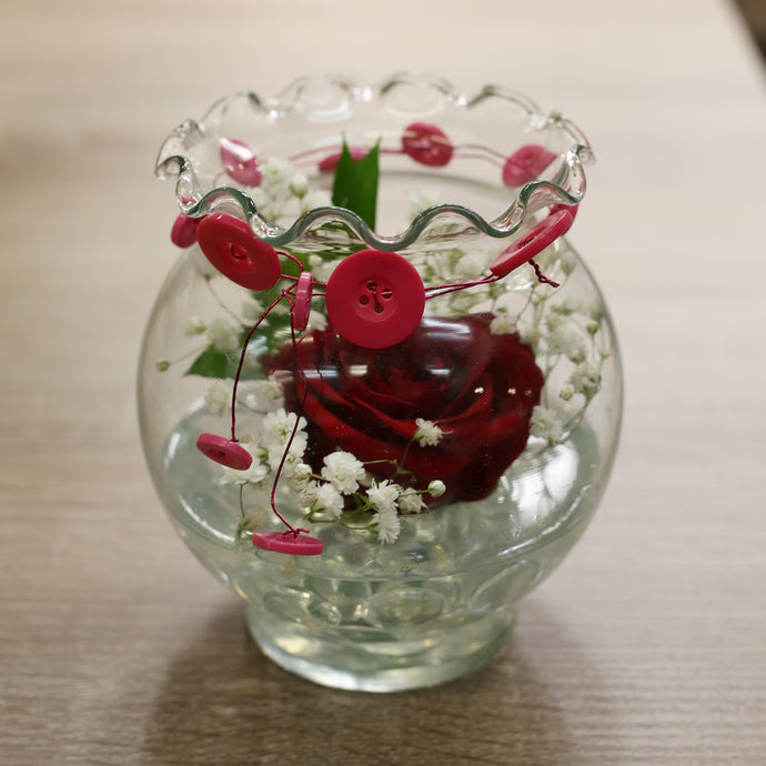 Small flower arrangement. One red rose surrounded but babies breath. The vase is clear and has a tie around the top.