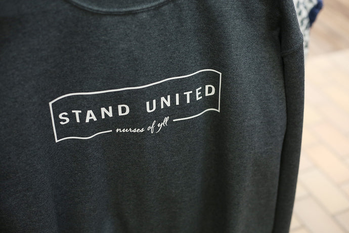 A dark grey sweater that has white text in the front that says, STAND UNITED nurses of YLL.