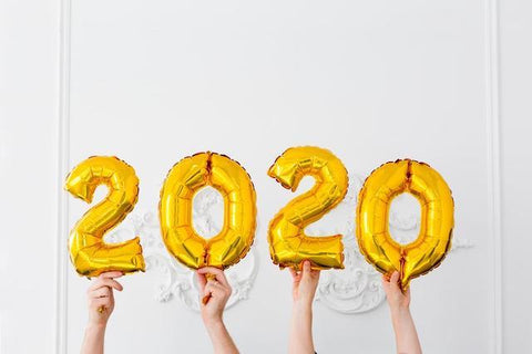 2020 in golden foil balloons, each number held up by a white hand