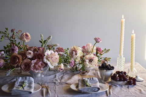Candles and dinner plates set beautifully amongst several floral arrangements designed by Ingrid Carozzi of Tin Can Studios.
