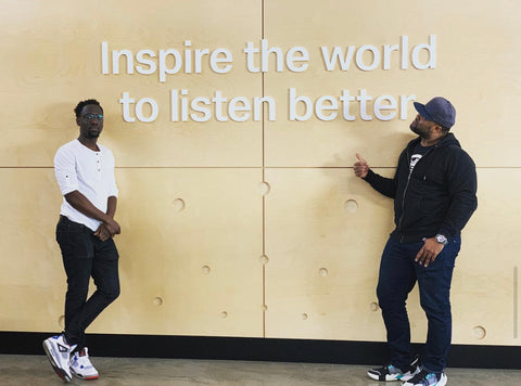 Wil B. and Kev Marcus of hip hop duo, Black Violin, lean casually against a wall that says: Inspire the world to listen better.