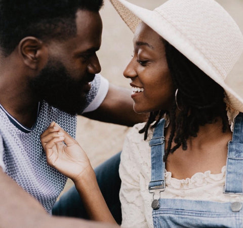 E, a black man with a beard, and Roe, a black women in a lovely white straw hat gaze lovingly into each other's eyes.