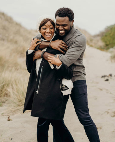 E, a black man lovingly embraces, Roe a black woman on a beach with a dune to their right.