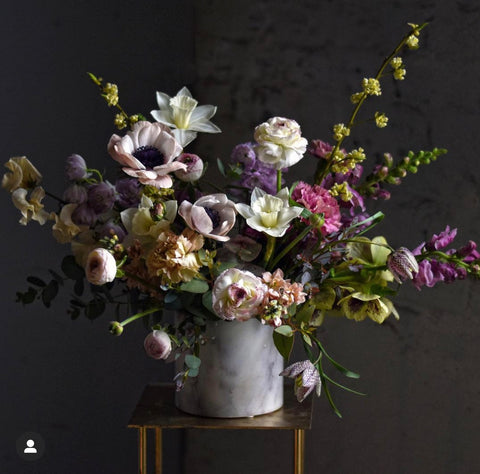 Dramatic floral arrangement in cream ceramic vase, styled like a Vermeer painting with dark, moody tones with fresh bright florals.