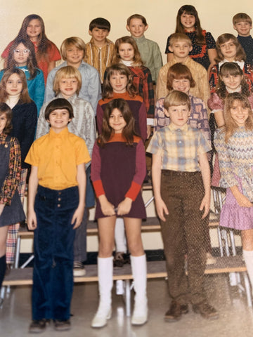 Joanne Heyman in white patent leather boots in a 70's class photos of white students in various plaids and cords.