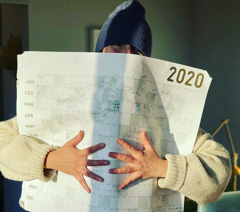 white woman in blue toque grasping an oversized 2020 wall calendar
