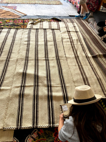 Sandra Dawn kneeling in front of a stack of Turkish kilim rugs in natural undyed color with two brown stripes close together, repeating pattern