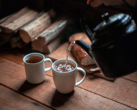 Two white mugs of tea, a black kettle pouring more into the mug to the right, sitting atop a wood table with a pile of wood in the upper left. photo by Harry Cunningham on Unsplash
