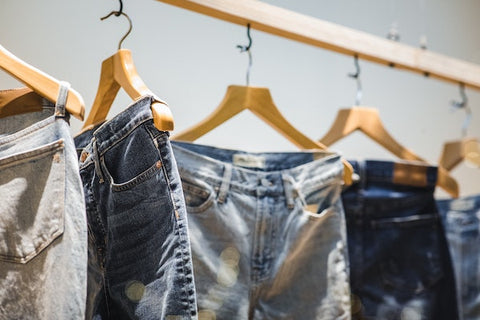 five pairs of blue denim jeans hanging on wooden hangers on a wooden rod
