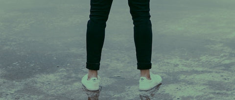 behind view of a person in black sweats and white sneakers