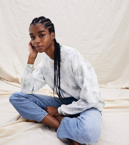 Young, beautiful black woman in a white with light green tie-dyed sweatshirt and light blue jeans, sitting crosse-legged.