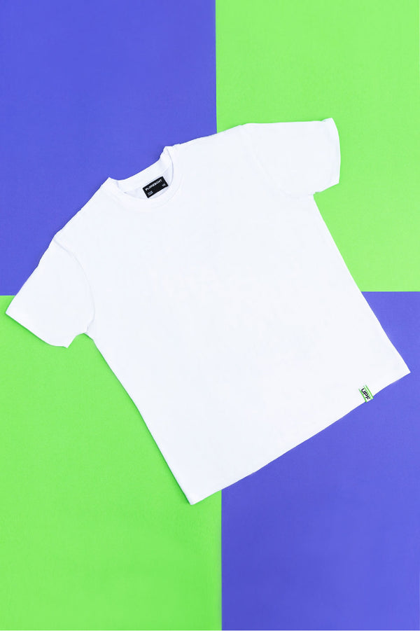 Flat lay of white UV resistant t-shirt with green UPF 50+ logo tab at hem on top of green and blue checkered background by Florescnt.