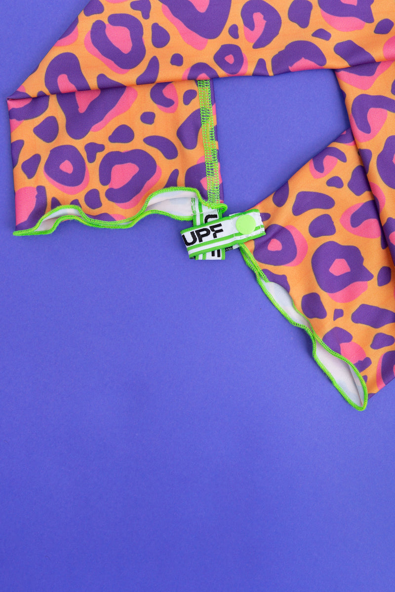 Flat lay of bright orange, pink and purple leopard print arm cooling covers and gloves with neon green stitching and interlocking UPF logo tabs by Florescnt