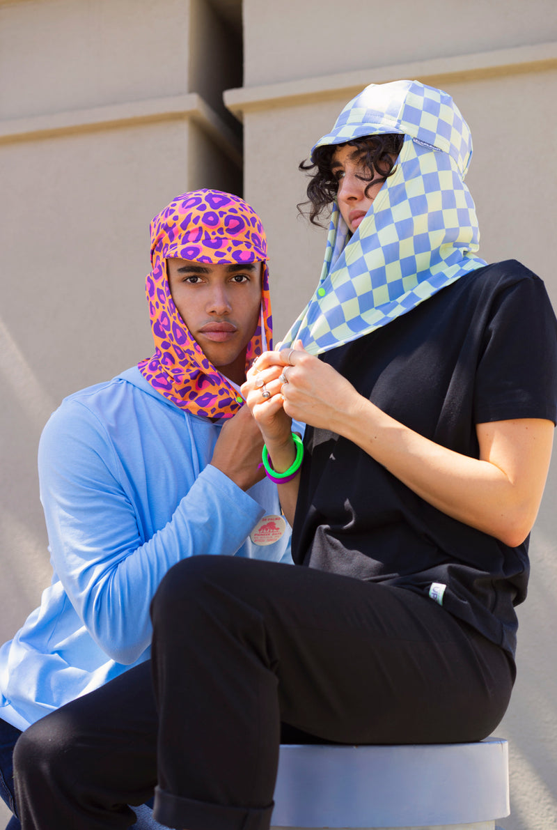 Young man and woman sitting in an outside courtyard, woman wears a cool sun hat with neck cover in blue and yellow checker print and man wears a bright orange and purple leopard print sun hat with neck flap by Florescnt