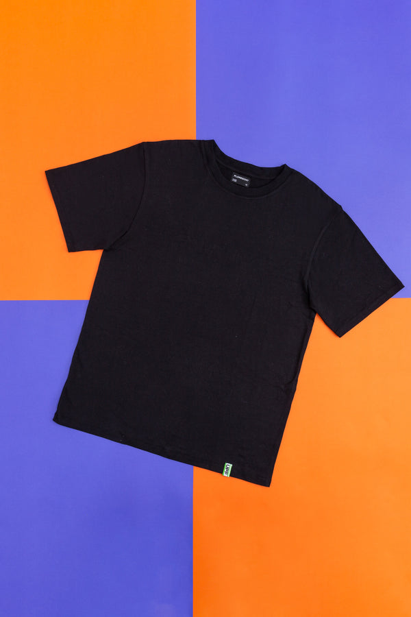 Flat lay of black sun resistant t-shirt with green UPF logo tab at hem on top of orange and purple checkered background by Florescnt.