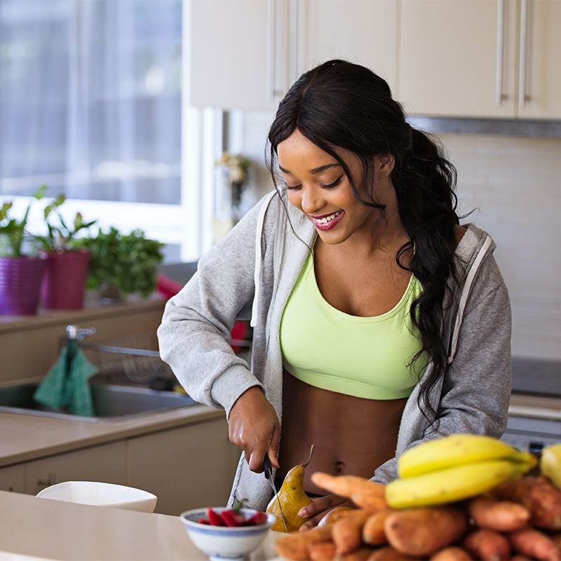 a person cutting a pear on a kitchen counter