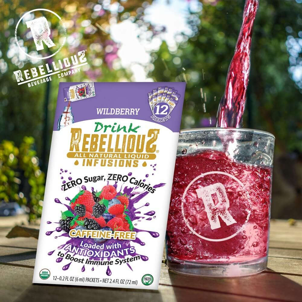 Rebellious Caffeine-Free Infusions (Wildberry) in 12-pack Sleeve and Pouring into Glass