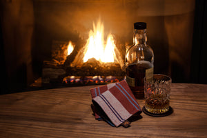 handkerchief and whisky on table in front of a fire