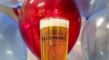 Descendants glass pint in front of red and blue balloons with medium light ale, Breweries Waterloo