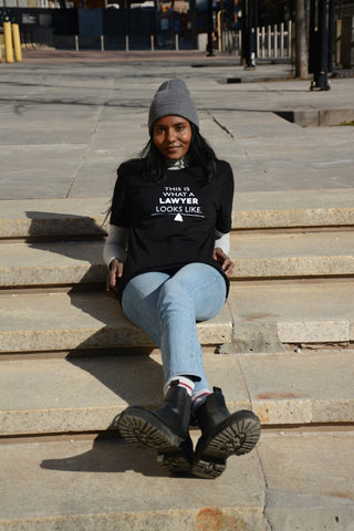 Lady Justice Apparel™ model wearing This is What a Lawyer Looks Like t-shirt reclining on steps of Superior Court of Justice in Toronto Ontario