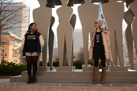 2 women wearing Lady Justice Apparel™  t-shirts at Pillars of Justice Sculpture Superior Court of Justice (361 University Avenue Courthouse)