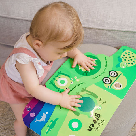 Baby using feed and hands to explore educational toy