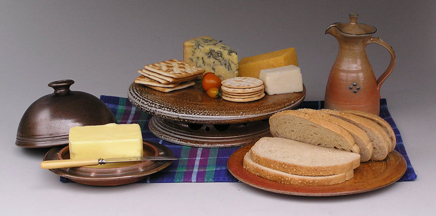 Large blue/black butter dish, elevated cheese platter, pale vinaigrette and side plate