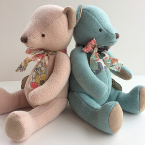 Beautiful Blue Teddy Bear - A timeless gift This beautiful blue teddy bear arrives in a floral cloth bag with a matching floral bow tie around his neck. This classic high quality teddy bear is timeless and will be treasured for years to come. Showng pink and blue teddy bears together sitting back to back.