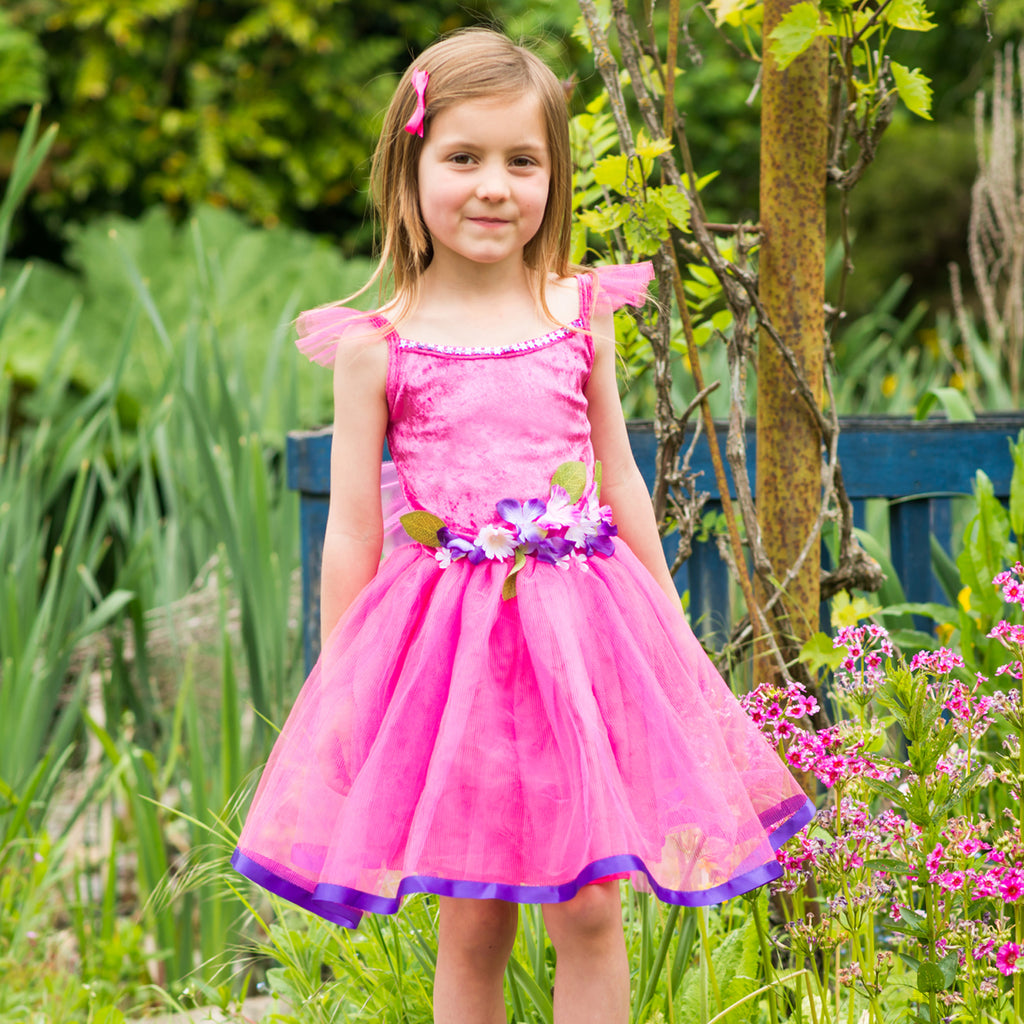 This cerise flower fairy dress makes a fabulous gift for girls who love dressing up. Your little one will feel fabulous in this colourful cerise flower fairy dress. Pretty pink and purple flowers embellish the waist and gorgeous purple ribbon edges the full net skirt. Soft petit net wings are halfway down the back of the bodice. Model wearing dress in garden