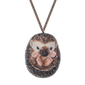 Hand-painted porcelain baby hedgehog necklace This curled up hedgehog necklace is a beautiful gift for someone who loves nature.  The superb intricate design features four pink feet, a black nose, and black eyes.  This necklace is from a range of hand-painted porcelain necklaces that have amazing detailed features.