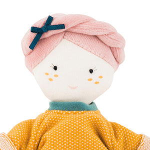 Moulin Roty Doll - French design, beautifully made, beloved gift! This soft 26cm Moulin Roty doll has a cheery expression, pink plaited velour hair with a black bow. She wears a bright orange jumper and white skirt. Her clothes are removable.  She will be a great addition to the family! Showing close up of doll's face