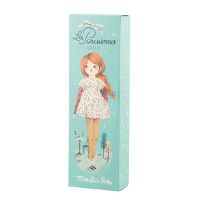 Mademoiselle Colette Doll By Moulin Roty - showing full picture  of gift box – ideal for special occasions. Colette has plush dark orange hair which is tied to the side with an emerald green bow. She is wearing a cute peach patterned dress with a yellow spotty box at the collar.
