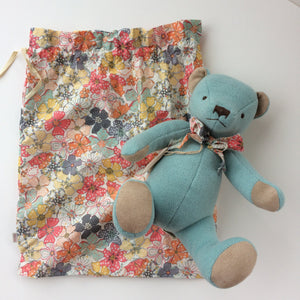Beautiful Blue Teddy Bear - A timeless gift This beautiful blue teddy bear arrives in a floral cloth bag with a matching floral bow tie around his neck. This classic high quality teddy bear is timeless and will be treasured for years to come. Made with soft velour light blue fabric, he has acrylic bead eyes and an embroidered nose and mouth. Showing bear and floral bag which the bear arrives in.