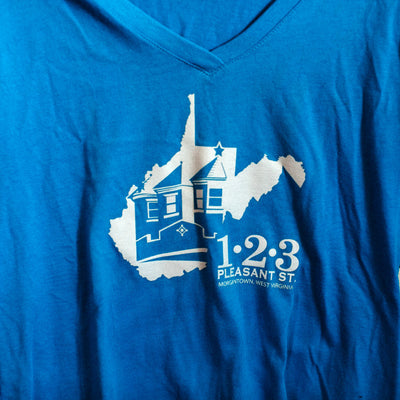 Blue shirt that has a white West Virginia State graphic with a building inside of it. It says 1 2 3 Pleasant Street Morgantown, West Virginia to the bottom right of it.