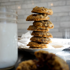 Stack of Trove Desserts handmade Chocolate Chunk Cookies with flaked Maldon sea salt on a white plate with a glass of milk
