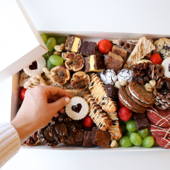 Trove Desserts Large Christmas Dessert Box with an assorted selection of seasonal holiday treats with a hand picking up a heart shaped linzer cookie out of the box