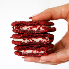 Hand holding a stack of three Trove Desserts Red Velvet Sandwich Cookies filled with cream cheese buttercream for Valentine's Day