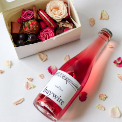 Trove Desserts Sweetheart Bundle including a mini grazing style dessert box for Valentine's day in pink and red theme and a 375mL bottle of Okanagan Crushpad's Haywire Baby Bub Sparkling Rose pictured with scattered rose petals