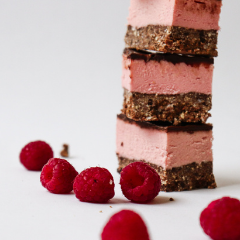 Stack of Trove Desserts famous hand made Raspberry Nanaimo Bars with fresh raspberries surrounding