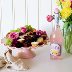 Trove Desserts Spring Signature dessert display with flowers, a pink cake stand, a bottle of French pink lemonade, and spring tulip flowers