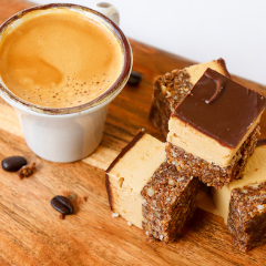 Trove Desserts handmade cappuccino Nanaimo bar made with a shot of Vancouver's JJ bean espresso displayed on a wooden charcuterie board
