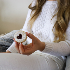 Trove Desserts co-founder dressed in all white monochrome outfit holding a heart cut-out shaped raspberry jam linzer sandwhich cookie