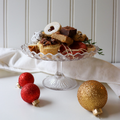 Trove Desserts Chrismas Dessert display with crystal cake stand filled with handmade seasonal desserts from Trove and a linen white napkin and Christmas glitter red and gold bobbles