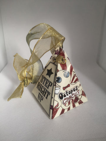 """red and white triangle shaped box with a golden ribbon, one side says """"STEP RIGHT UP"""" the other has an octopus with a bowtie and says """"OCTOPUS CIRCUS"""""""