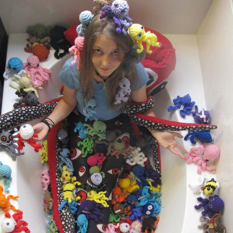 a person in a bathtub of octopus stuffed animals.